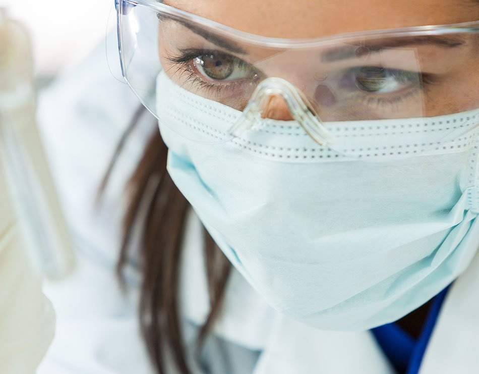 Female Bemis Healthcare Packaging Europe employee wearing eye goggles and face mask